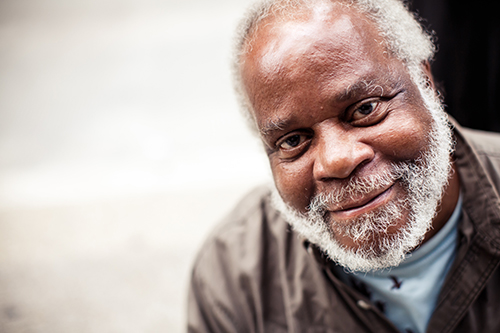 African American man with grey beard smiling at the camera